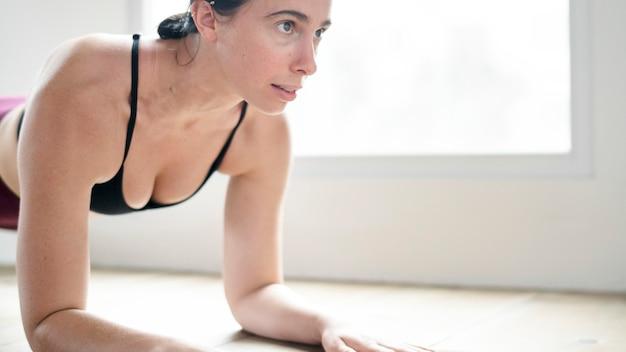 Donna sportiva che fa la tavola del gomito sul pavimento
