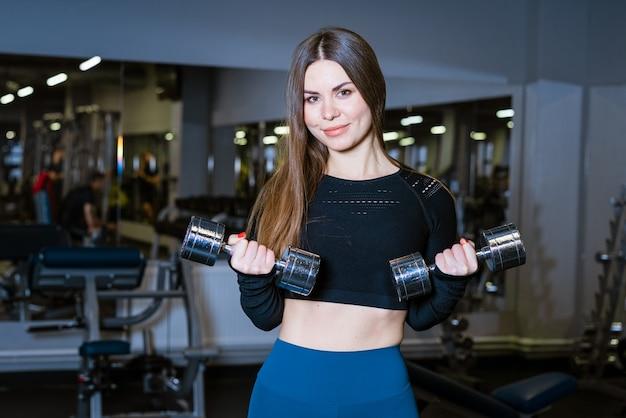 Donna sportiva che fa riscaldamento in palestra con manubri in mano donna in palestra che fa esercizi addominali in ...