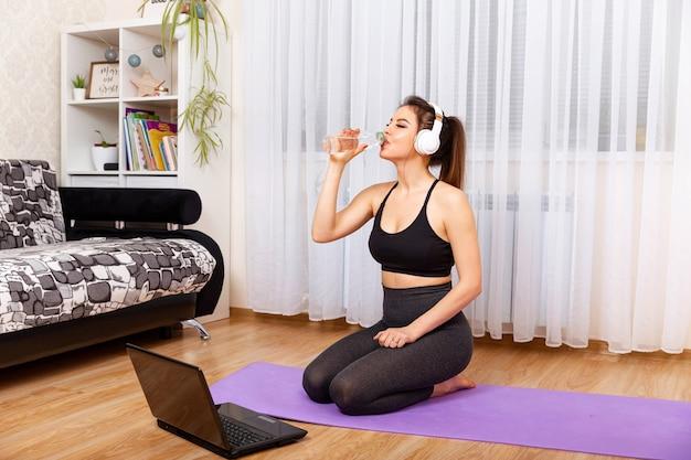 Acqua potabile della donna allegra e seduta sul tappetino fitness