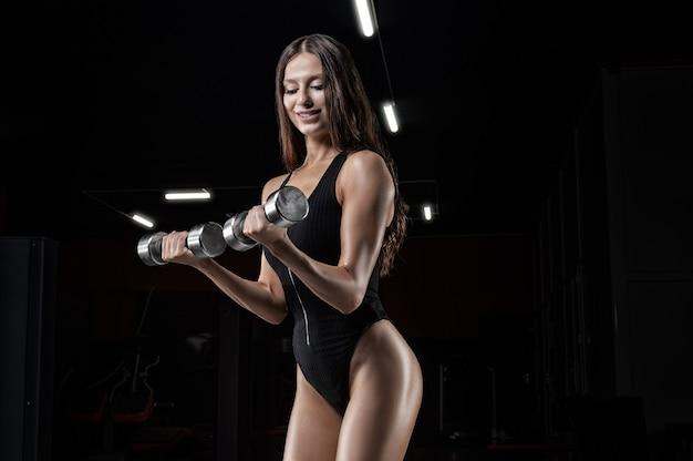 Donna allegra in palestra esegue un esercizio con manubri. concetto di fitness.