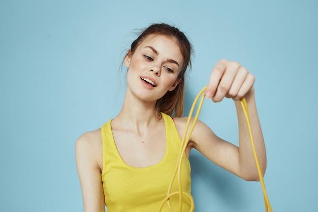 Donna allegra che tiene una parete blu di ginnastica di esercitazione della canottiera gialla della corda per saltare.