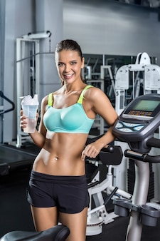 Una donna sportiva tiene in mano un bicchiere d'acqua. centro fitness.