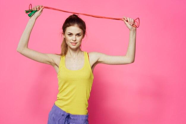 Donna allegra che salta la corda amico esercizio canotta gialla allenamento rosa.