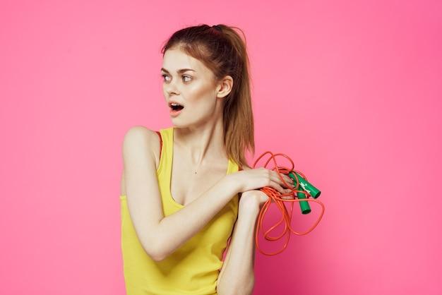 Donna allegra che salta la corda nello stile di vita di allenamento di sfondo rosa canottiera gialla delle mani.