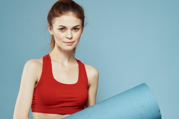 Donna allegra in stuoia canotta rossa per esercizi di allenamento lifestyle sfondo blu.