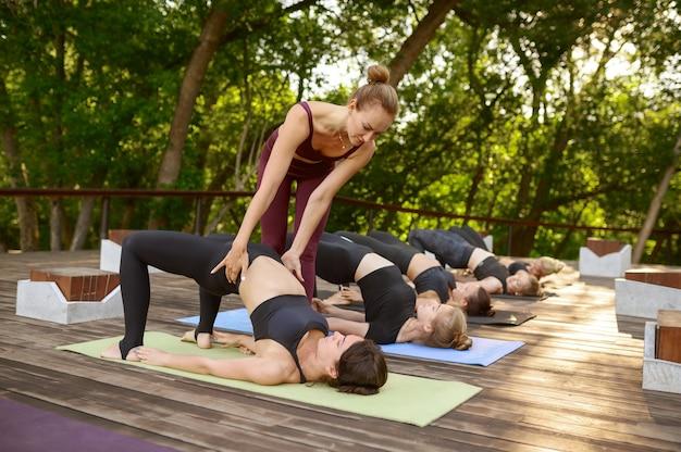 Donne allegre sulla formazione yoga di gruppo con istruttore nel parco estivo. meditazione, lezione in forma sull'allenamento all'aperto
