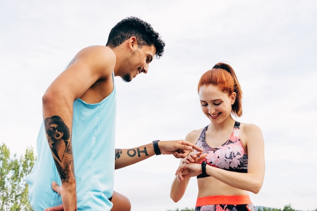 Giovani coppie allegre che hanno una pausa controllando i dati che emergono dallo smartwatch