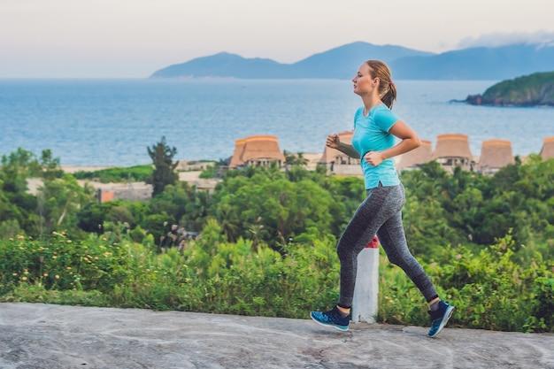 Una giovane donna sportiva è impegnata a correre contro il mare