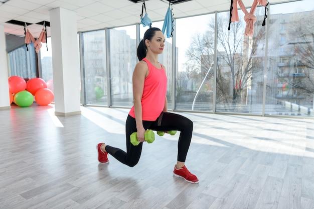 Giovane donna allegra con manubri facendo esercizio in palestra. allenamento del corpo fitness. uno stile di vita sano