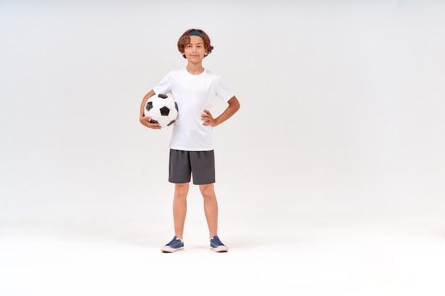 Attività sportive foto a figura intera di un adolescente felice che tiene in mano un pallone da calcio che guarda la telecamera e
