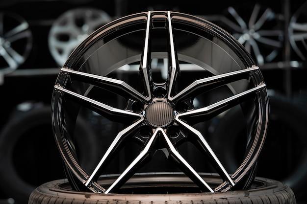 Cerchio in lega sportiva con copertura in carbonio, nella hall del negozio di auto sullo sfondo delle ruote. vista frontale.