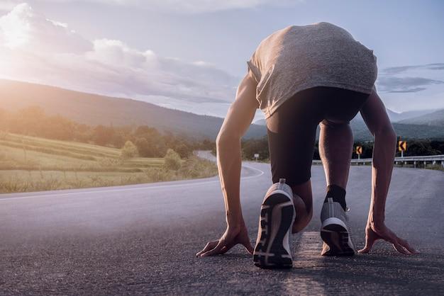 Sfondo sportivo. piedi del corridore che corrono sul primo piano della strada sulla scarpa. corridore in partenza.