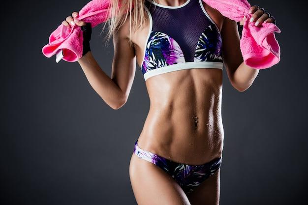 Disidratazione sportiva. primo piano potato di una donna sbalorditiva di forma fisica allo studio su oscurità