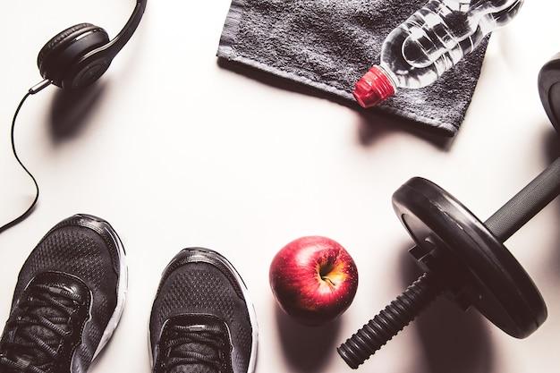 Attrezzatura sportiva, mela e bottiglia d'acqua