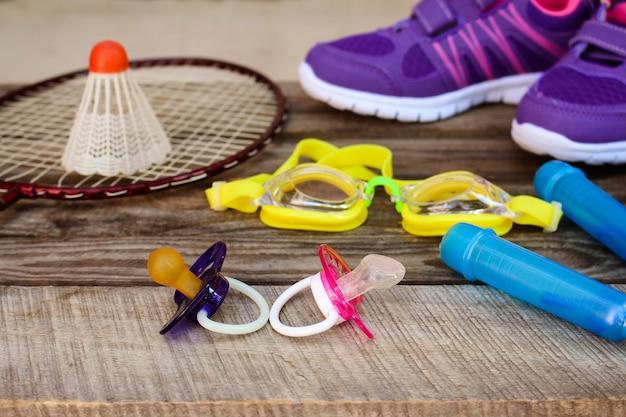Attrezzature sportive: l'uccellino è sulla racchetta, saltando la corda, occhiali da nuoto e scarpe da ginnastica su fondo di legno