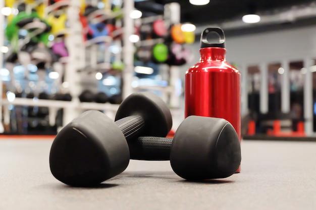 Manubri di attrezzature sportive e bottiglia di acqua rossa in club sportivo o palestra e sala fitness.