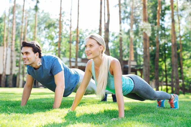 Esercizio sportivo. felice bella coppia push up mentre si allena nel parco