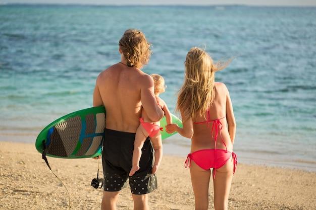 Mette in mostra la famiglia papà mamma e figlia che camminano sulla spiaggia