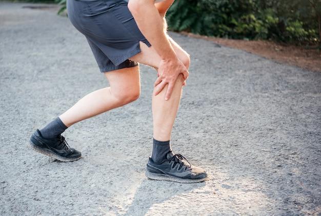 L'uomo di fitness sportivo soffre di dolore al ginocchio durante la corsa o il jogging