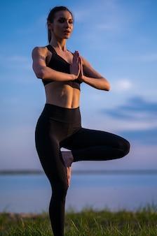 Ragazza di sport che fa yoga sulla spiaggia