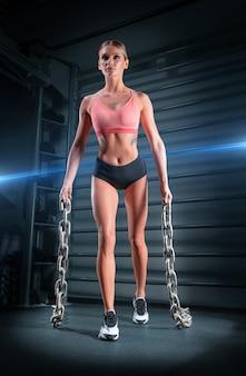 Ragazza sportiva si allena in palestra portando catene di metalli pesanti nelle sue mani.