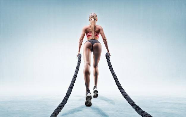 Ragazza sportiva si allena con le corde. vista posteriore.
