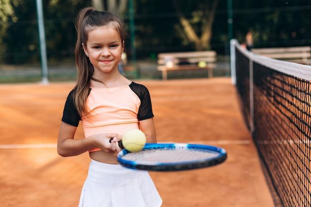 Mette in mostra la ragazza con una racchetta e una palla da tennis in sue mani sul campo da tennis Foto Premium