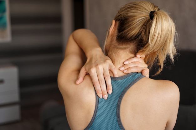 Concetto di infortunio sportivo. ragazza atletica che sente dolore al collo. dolore dopo l'allenamento a casa
