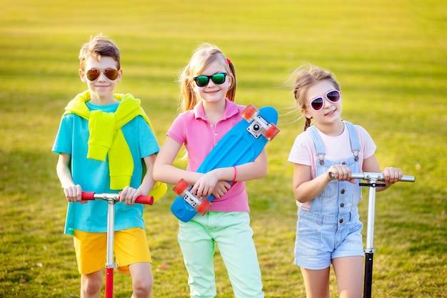 Mette in mostra i bambini con uno skateboard nel parco in primavera. sport all'aperto.
