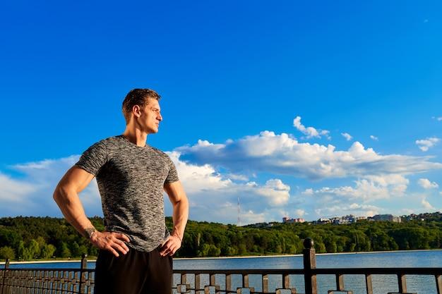 Figura del corpo dell'uomo sportivo con il cielo blu sullo sfondo sguardo fiducioso
