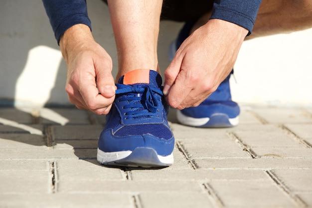 Lacci delle scarpe di sincronizzazione delle mani dell'uomo di sport