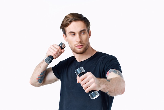 L'uomo sportivo è impegnato nel fitness su uno sfondo bianco con manubri nelle sue mani