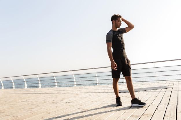 Uomo di sport all'aperto sulla spiaggia che osserva da parte