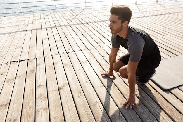 L'uomo di sport all'aperto sulla spiaggia fa esercizi sportivi