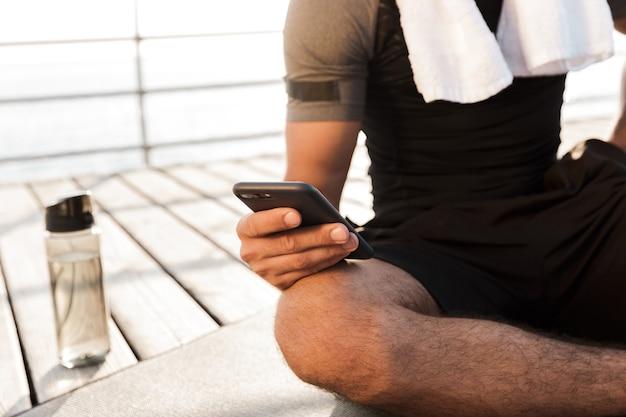 Uomo di sport all'aperto sulla spiaggia che si siede vicino alla bottiglia con acqua sul tappeto utilizzando smartphone