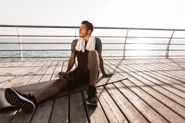 Uomo di sport all'aperto sulla spiaggia che si siede vicino alla bottiglia con acqua sul tappeto