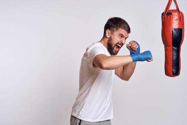 Palestra di esercizio del sacco da boxe della maglietta bianca dell'uomo di sport