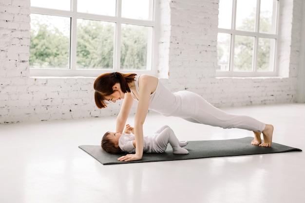 La madre dello sport è impegnata in fitness e yoga con un bambino, facendo tavola e push up sul tappetino nero