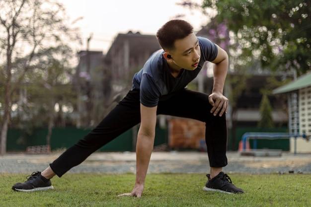 Concetto di sport e ricreazione un giovane maschio che fa riscaldamento allungando ogni parte del suo corpo come preparazione prima dell'esercizio.