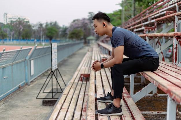 Concetto di sport e ricreazione un giovane maschio seduto su una tribuna al confine di uno staduim.