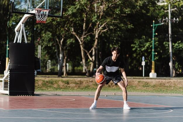 Concetto di sport e ricreazione un giovane giocatore di basket maschile in possesso di un pallone da basket da solo sullo sfondo del campo da basket.