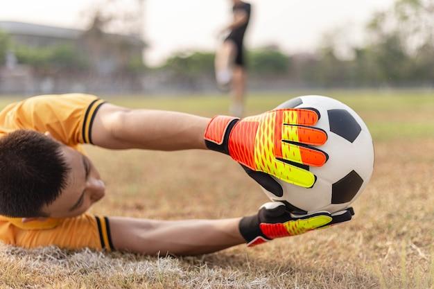 Concetto di sport e ricreazione un giovane portiere maschio che usa entrambe le mani per prendere la palla per impedire alla squadra avversaria di segnare.