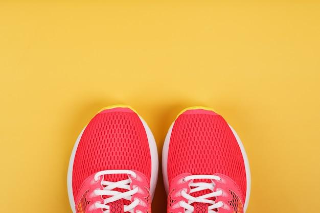 Scarpe da ginnastica sportive, rosa su sfondo giallo con spazio libero. vista dall'alto, concetto minimalista