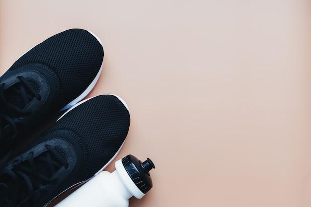 Scarpe da ginnastica sportive per correre, borraccia su fondo beige. foto di alta qualità