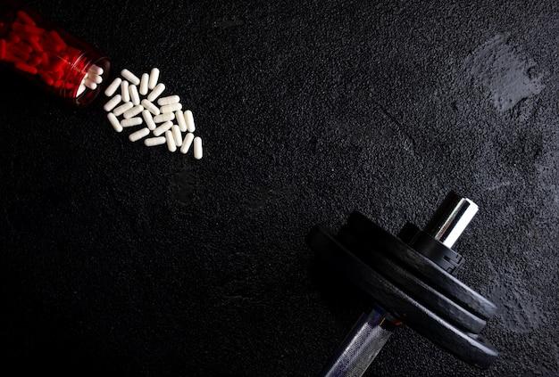 Integratori sportivi con pesi sulla superficie scura. medicinali
