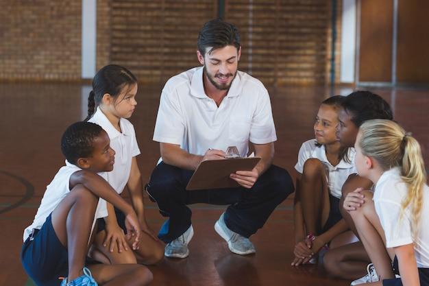 Insegnante di sport che ha discussione con i suoi studenti