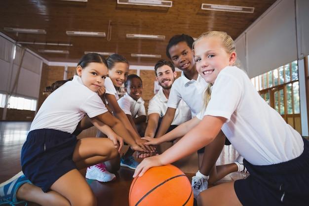 Insegnante di sport e bambini della scuola che formano la pila della mano nel campo da pallacanestro