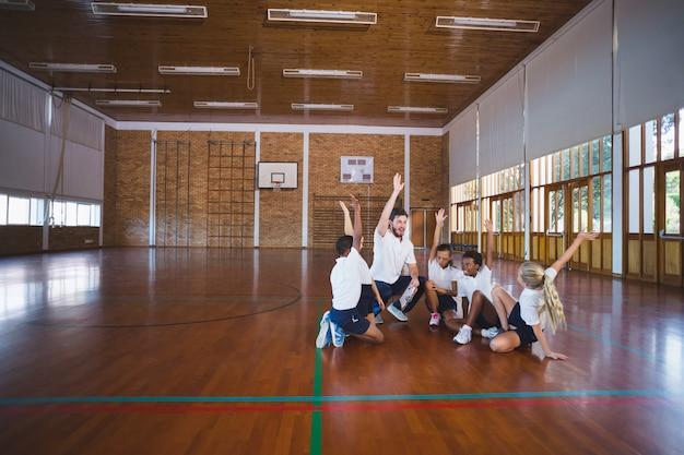 Insegnante di sport e bambini della scuola che giocano nel campo da basket