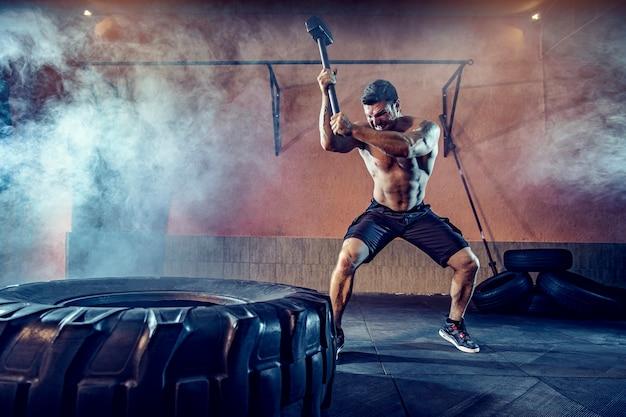 Allenamento sportivo per la resistenza, l'uomo colpisce il martello. allenamento di concetto.