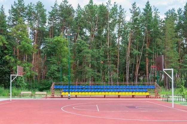 Tribuna sportiva di sedili in plastica gialla e blu sul campo da basket vuoto all'aperto. concetto di sport di strada. arena all'aperto vuota.